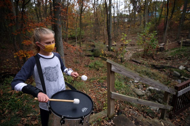 Colonial Hills Elementary School sixth-grader Zoe Kuzio and other members of a samba band warm up for an opening ceremony Oct. 28 at the new outdoor-learning space in a 7-acre ravine behind the school at 5800 Greenwich St. It includes seating areas, a demonstration table and a V-shaped awning over the main area that collects rainwater and allows the outdoor space to be used in all weather conditions. It also features a walking bridge over a creek and volunteer-maintained trails.