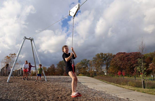 Hannah Berger, 8, plays on a miniature zip line at Seldom Seen Park on Oct. 23. The 23-acre park, on the north side of Seldom Seen Road and west of Liberty Street and the railroad tracks in Powell, opened Oct. 21.