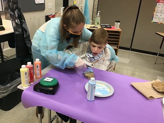 Nicole Holder, an intervention specialist and multiple-disabilities teacher at Jones Middle School, works with Reid Hudson to paint a positivity rock for a service-learning project. Students are painting positive messages on rocks then placing them throughout the community.
