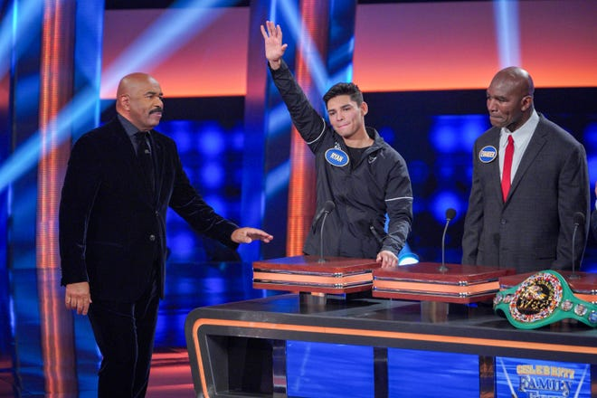 "Ryan Garcia, center, waives to the studio audience as the professional boxer from Victorville stands next to host Steve Harvey, left, and teammate Evander Holyfield on the set of ""Celebrity Family Feud,"" which aired Thursday night, Oct. 29, 2020, on ABC."