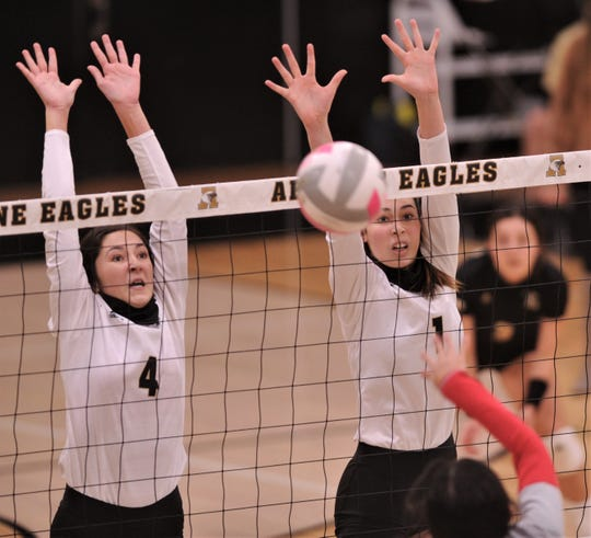 Abilene High's Aven Horn (4) and Jadyn Hernandez defend on the net as an Odessa High player hits the ball. AHS defeated the Lady Bronchos on Wednesday at Eagle Gym with 25-16, 25-18, 22-25, 25-19 in District 2-6A's volleyball game.
