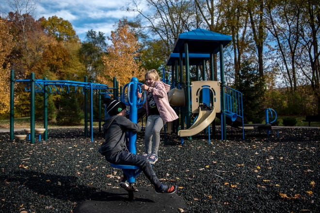 Siblings Reid Dingman, 8, and Reagan Dingman, 6, play on a Whizzy Dizzy at Historic Bridge Park on Wednesday, Oct. 28, 2020 in Battle Creek, Mich.