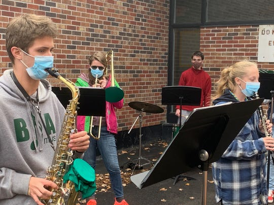 Advanced wind ensemble students Nathaniel Cobb, Sydney Ward, Ben Briggs and Aria Garceau brave the elements in order to play music Oct. 27, 2020 at Bellows Free Academy - St. Albans. Wind instruments were singled out for disseminating respiratory droplets during the pandemic and require extra safety precautions to be taken in order to play.