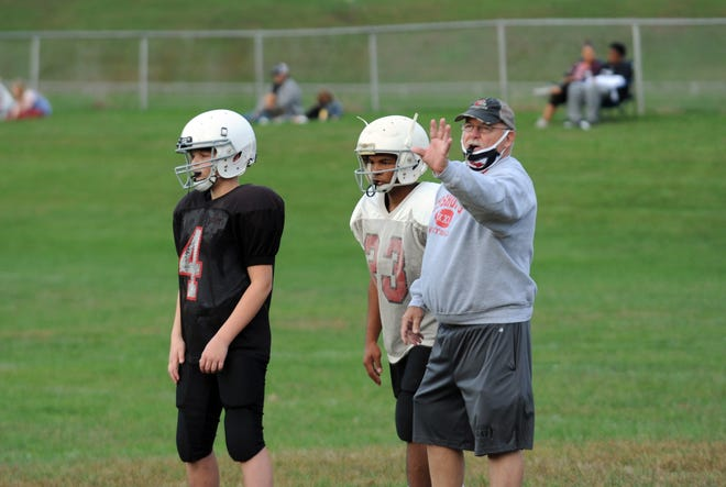 Gary Forbes (right) instructs players during practice with Coshocton Junior High football. Forbes has decided to retire this season after serving in a variety roles during a nearly 40-year career.