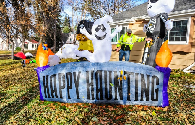 Steven Fox inflates his Halloween decorations after remnants of last weekend's snow finally melted away, Thursday, October 29, 2020.