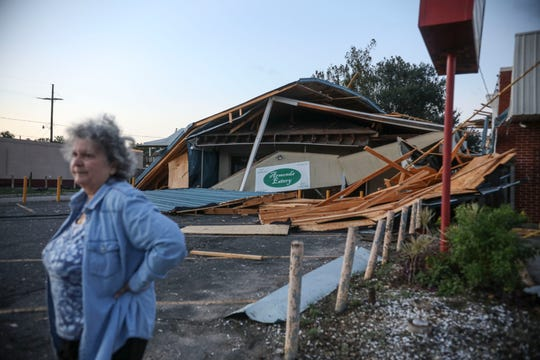 A woman stands in front of a destroyed restaurant after Hurricane Zeta on October 29, 2020, in Chalmette, Louisiana. A record seven hurricanes have hit the gulf coast in 2020 bringing prolonged destruction to the area.
