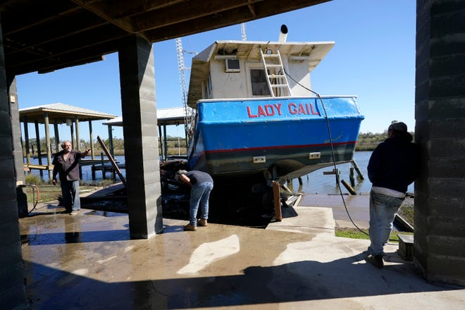 Boat owner Ricky Mitchell, center, and his friend Buck, left, no last name given, survey damage to his boat that washed up against the home of Ray Garcia, in Lakeshore, Miss., Thursday, Oct. 29, 2020. Hurricane Zeta passed through Wednesday with a tidal surge that caused the boat to become unmoored.