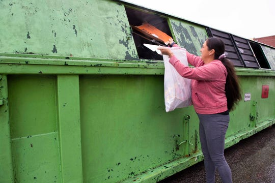 Miriam Garcia places paper recycle items at one of the recycling locations  in Jackson, Tenn., Thursday, Oct. 29, 2020.