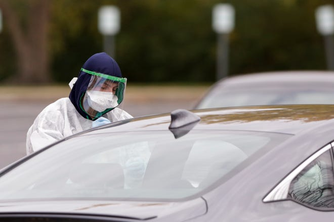 COVID-19 tests are administered at a state-run drive-through site in a parking lot at White Horse Christian Center, 1780 Cumberland Ave., Thursday, Oct. 29, 2020 in West Lafayette.