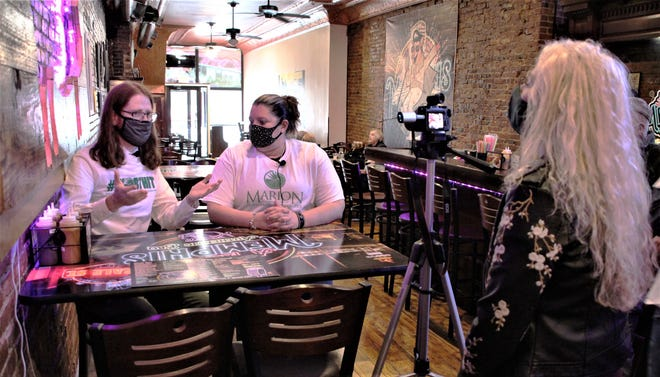 Ander Christensen, left, who has gained social media fame as the Saucy Nugs Guy, interviews A Taste of Memphis co-owner Shannah Turner, center, during a stop at the Marion restaurant on Wednesday, Oct. 28, 2020. Christensen was in Marion as part of a tour in the wake of his tongue-in-cheek address about boneless chicken wings to the Lincoln (Nebraska) City Council.