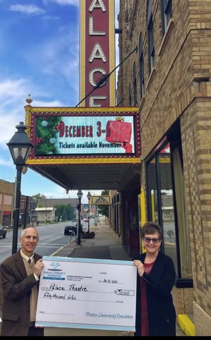 Dean Jacob, president and CEO of Marion Community Foundation, presents a grant of $50,000 from the Wopat Community Fund to Bev Ford, executive director of the Marion Palace Theatre.