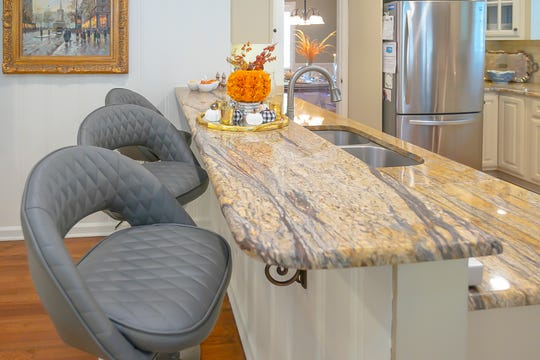 Additional seating at the breakfast bar features granite countertops and cushioned bar stools.