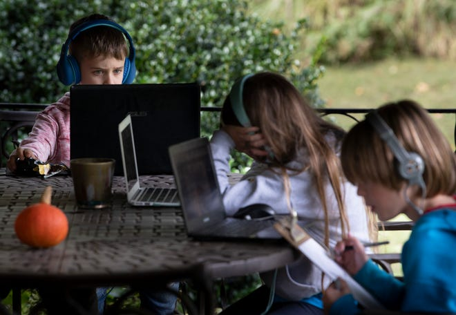 A 8-year-old student participates in an online class as his education pod mates work on school lessons Sept. 29 in Nashville, Tenn. Their families came together to create a learning pod for their children to learn remotely during the coronavirus pandemic.