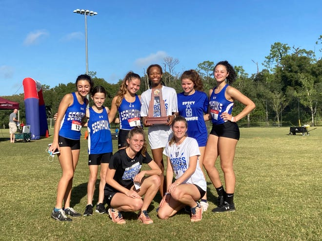 The Community School girls cross country team celebrate their victory at the Class 1A-District 12 cross country meet at Ave Maria on Thursday. The Seahawks edged Village School and Donahue Academy for the title.