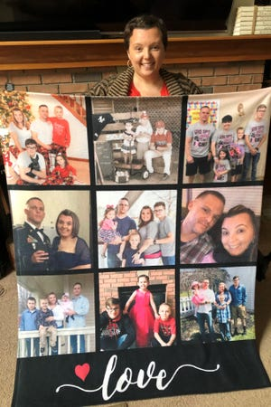 Shanay Nye of Heath, who is celebrating her one-year anniversary of being a breast cancer survivor, shows off a blanket full of family photos that friend Megan Harter got her for last Christmas.