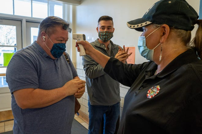 Dawn Kryder checks Chuck Griego's temperature while Elias Trujillo sanitizes his hands, before early voting at the San Miguel County Clerk's office in Las Vegas, New Mexico.