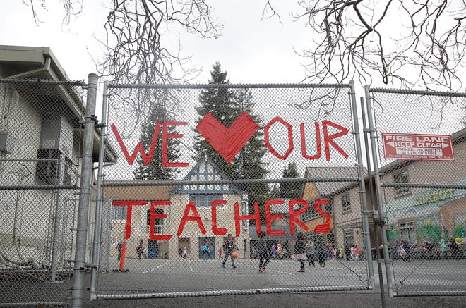In this March 4, 2019, file photo, a sign supporting teachers is shown on a fence outside of Chabot Elementary School in Oakland, Calif. Alameda County is allowing middle and high schools to reopen.