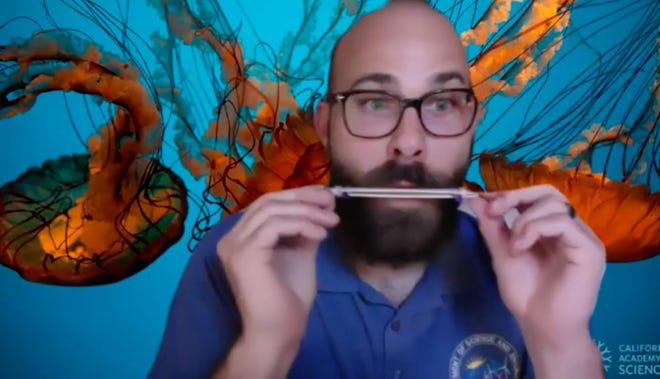 Science teacher Philip Hudec demonstrates a homemade musical instrument.