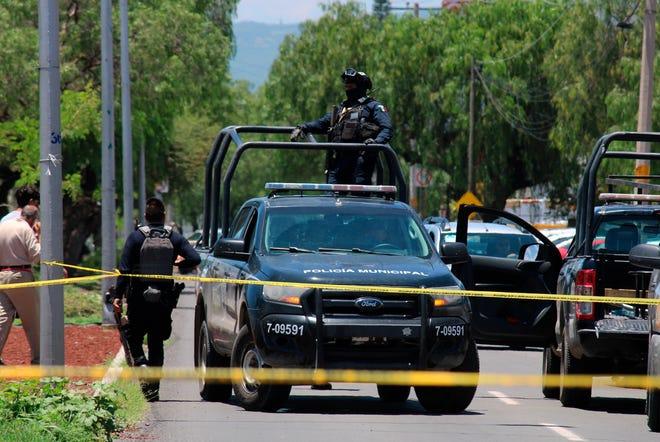 Miembros de la Guardia Nacional y policía estatal vigilan el lugar donde fueron hallados restos de 59 personas en el estado de Guanajuato.