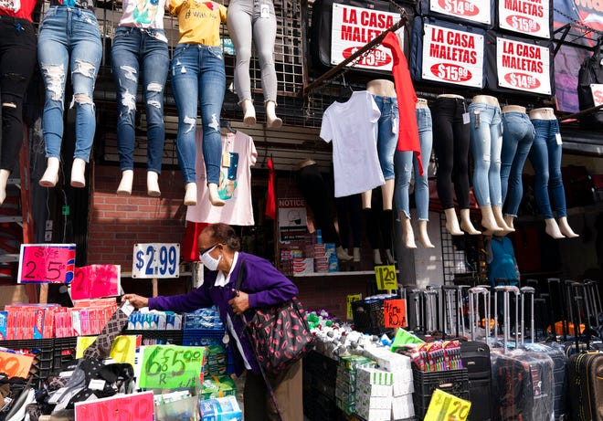 FILE - In this Sept. 25, 2020 file photo, a woman shops at a clothing store in New York. The U.S. economy grew at a sizzling 33.1% annual rate in the July-September quarter — by far the largest quarterly gain on record — rebounding from an epic plunge in the spring, when the eruption of the coronavirus closed businesses and threw tens of millions out of work.  (AP Photo/Mark Lennihan, File)