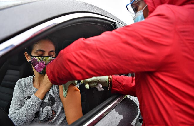 Sayra Keelan, of Conewago Township, is administered a flu shot by Jasmin Brown, L.P.N., while sitting inside her car during a drive-thru flu shot clinic at WellSpan Hayshire Family Practice in Manchester Township, Thursday, Oct. 29, 2020. Dawn J. Sagert photo