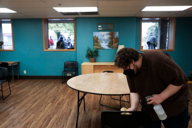 Jeshua Fagan, who is volunteering as part of an internship, wipes down tables and chairs in the dayroom at ARCHES Project in Salem, Oregon on Thursday, Oct. 29, 2020. The dayroom is cleaned hourly as precaution for COVID-19.