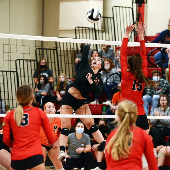Nora DuPerow spikes the ball over Erin Scurlock during the first set of New Lexington's 13-25, 23-25, 25-23, 15-25 loss in a Division III sectional final on Wednesday.