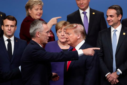 NATO Secretary General Jens Stoltenberg, front left, speaks with President Donald Trump, after a group photo at a NATO leaders meeting at The Grove hotel and resort in Watford, Hertfordshire, England, on Dec. 4, 2019.