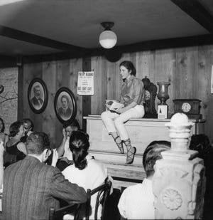 "Poet Diane di Prima sits atop a piano and reads from her collection ""This Kind of Bird Flies Backwards"" to an appreciative audience at the Gas Light Cafe in New York on June 28, 1959. Di Prima died Oct. 28, 2020, at 86,"