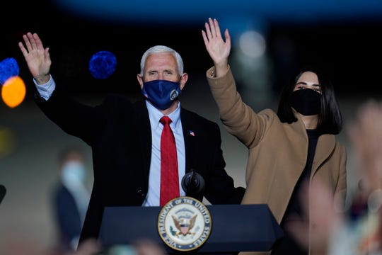 Vice President Mike Pence and his daughter Audrey acknowledge his supporters after speaking at a campaign event Wednesday in Flint, Michigan.