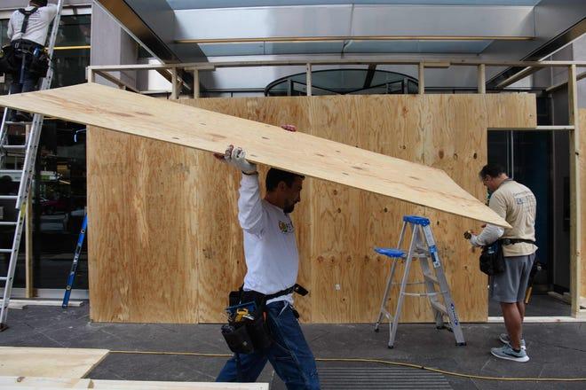 Рабочий несет деревянную доску, когда офисные здания и магазины в Вашингтоне, округ Колумбия, заколочены 28 октября 2020 года, в преддверии возможного насилия после выборов.