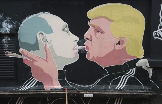 A mural depicting then-President-elect Donald Trump, right, blows marijuana smoke into the mouth of Russian President Vladimir Putin on the wall of restaurant in Vilnius, Lithuania, on Nov. 23, 2016.
