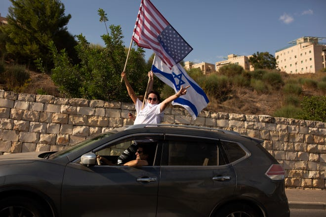Supporters of U.S. President Donald Trump for re-election wave an American and an Israeli flag from a car headed for a rally outside of the U.S. Embassy, in Jerusalem, Tuesday, Oct. 27, 2020.