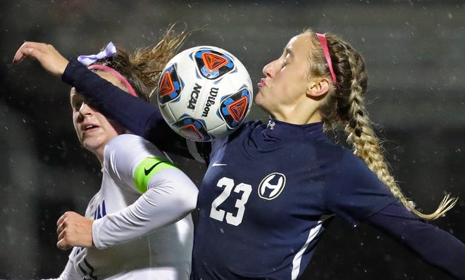 Hoban forward Miriam Szijarto, right, makes a play for the ball against Hudson's Kali Sweet during the second half of a Division I district final soccer game, Thursday, Oct. 29, 2020, in Akron, Ohio. [Jeff Lange/Beacon Journal]