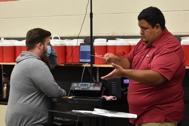 Ardmore band director T.J. Tolbert manages recording equipment while colleague John Moreno conducts the high school concert band Friday.