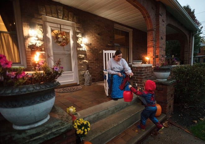 Dawn Larson hands out candy to trick-or-treaters from the front porch of her Fifth Avenue home Thursday night in Beaver Falls.