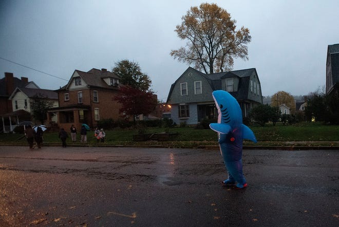 A person dressed as a shark wanders along Fifth Avenue during trick-or-treating Thursday night in Beaver Falls.