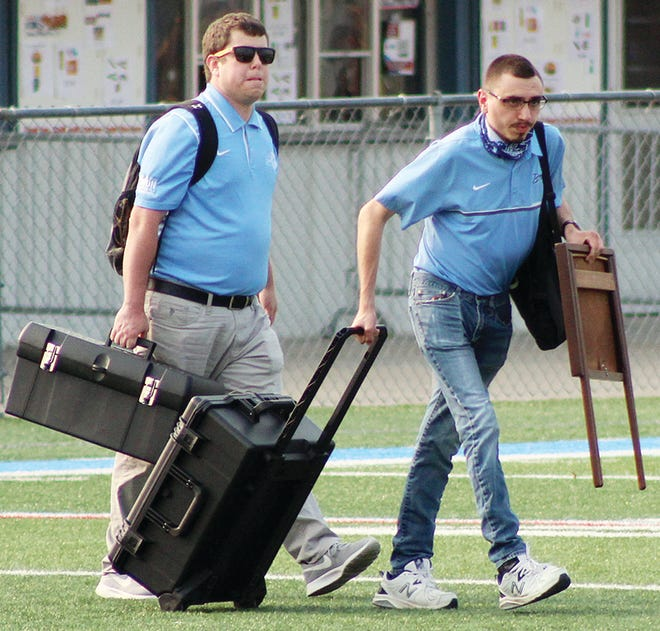 Trey Stumpff, right, prepares to help set up the broadcasting equipment for KWON radio during football action earlier this fall. At left is KWON Sports Director Even Fahrbach.