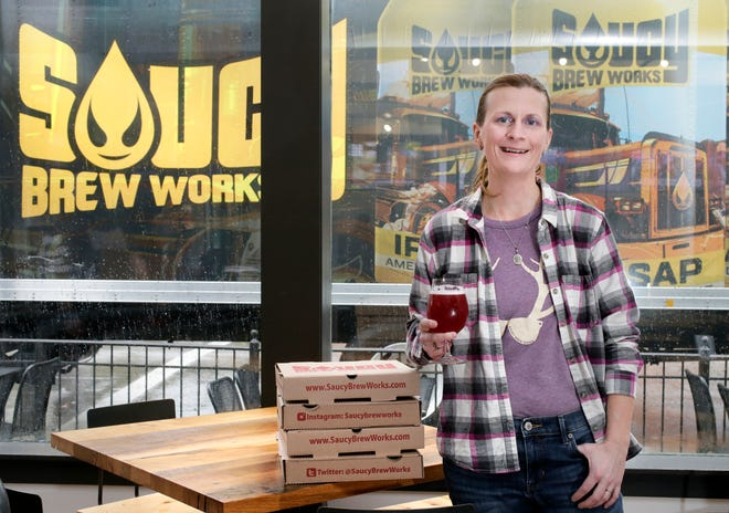 Jamie Young raises a glass at Saucy Brew Works' new location on West 3rd Avenue in Columbus.