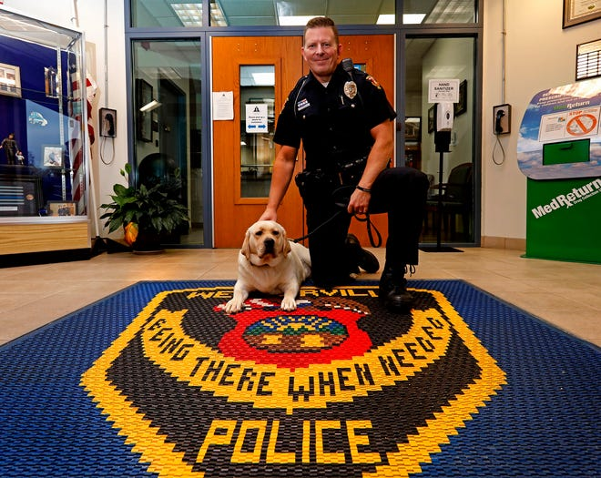 Westerville police officer Mark Wojciehowski poses Friday with Chloe, a 14-month-old, yellow English Labrador retriever who is the department's first therapy dog.  Wojciehowski is Chloe's handler .