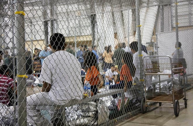 FILE - In this June 17, 2018, file photo provided by U.S. Customs and Border Protection, people who've been taken into custody related to cases of illegal entry into the United States, sit in one of the cages at a facility in McAllen, Texas. A federal judge on Thursday, Oct. 22, 2020, urged the Trump administration to do more to help court-appointed researchers find hundreds of parents who were separated from their children after they crossed the U.S.-Mexico border beginning in 2017. (U.S. Customs and Border Protection's Rio Grande Valley Sector via AP, File)