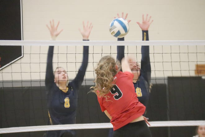 Crookston's Chloe Bruley (left) and Mallorie Sundeen (right) try to block a Red Lake County Central shot in Thursday night's match in Oklee. The Mustangs won in three sets, 25-16, 25-22 and 25-22.