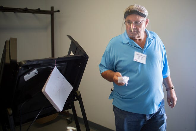 Voting Machine Operator Larry Venable wipes down a voting machine in an effort to prevent the spread of the coronavirus on the first day of early voting for the August State and Federal Primary and County Election at the Maury County Election Commission in Columbia, Tenn., on Friday, July 17, 2020.