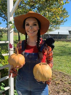Extension 4-H Agent Alisha Hutchinson, ready for Halloween, holds the pumpkin variety 'La Estrella.'