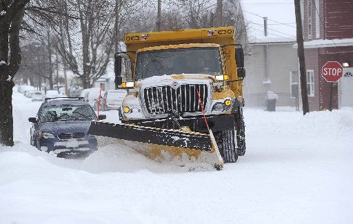 A City of Erie plow truck clears snow from around a parked car in the 600 block of East 25th Street in Erie in this file photo.  The city's winter parking rules go back into effect on Monday.