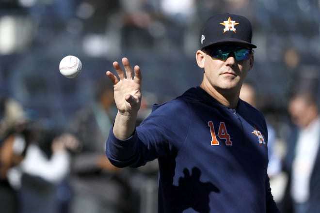 Then-Houston Astros manager AJ Hinch reaches for a ball before Game 3 of the 2019 American League Championship Series against the New York Yankees in New York. The Detroit Tigers have hired Hinch to be their new manager, giving him a chance to return to a major league dugout after he was suspended and fired by Houston in the wake of the Astros' sign-stealing scandal.