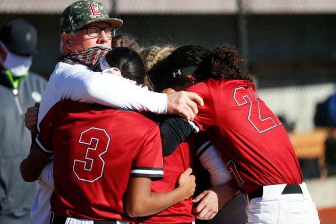 Lee's Summit North coach John Gage comforts his team after they lost to the Columbia Rock Bridge Bruins in the Class 5 State Softball Championship at Killian Sports Complex in Springfield Friday.