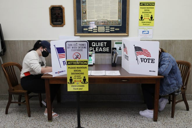 Taylor Evans, left, and Alexa Jaeger, right, fill out their ballots Friday as Iowa voters visit the county auditor's offices to vote early in person at the Des Moines County Courthouse in Burlington. The period for absentee in-person voting runs to Monday, Nov. 2.