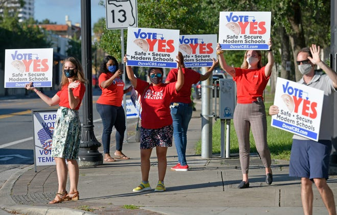 Volunteers wave signs supporting the half-cent sales tax for schools while standing on the sidewalk near the early-voting site in San Marco. Duval Citizens for Public Schools has used grass-roots activism along with television ads to appeal to voters.