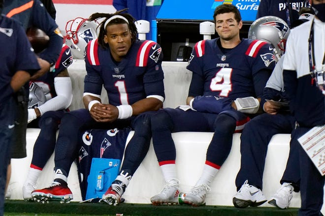 Patriots quarterbacks Cam Newton, left, and Jarrett Stidham sit on the bench during the game against the San Francisco 49ers earlier this season. The question is who will remain sitting and who will start when the Pats face the Buffalo Bills on Monday.